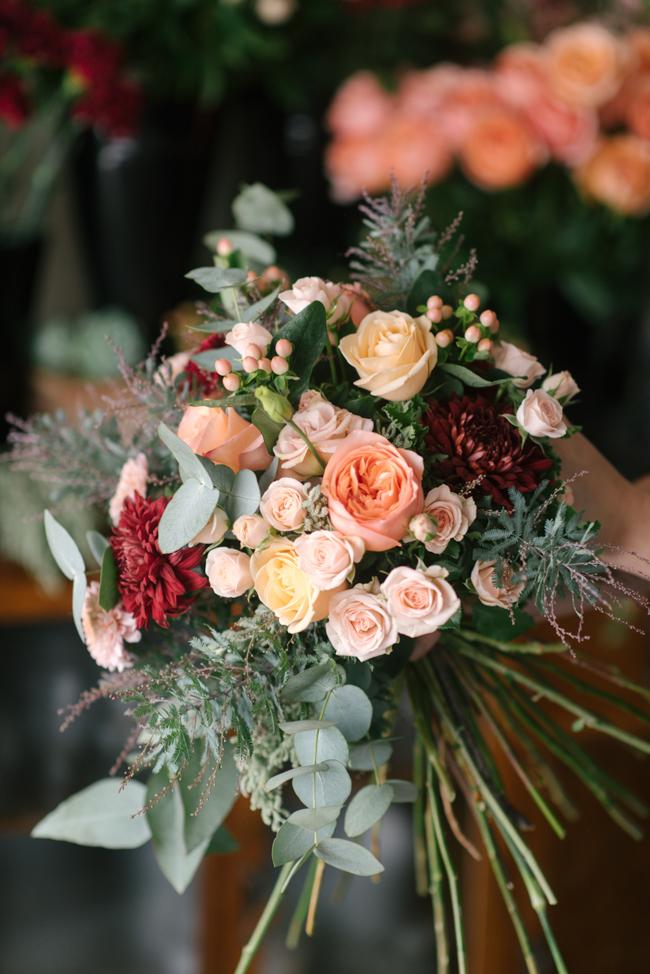 An Organic Hand-Tied Bridal Bouquet in Blush, Peach & Marsala