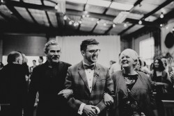 Groom walking down the aisle with his parents