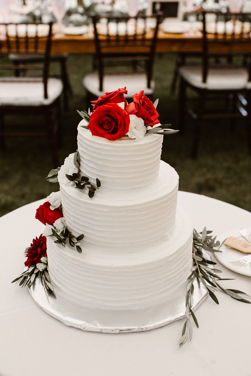 White Wedding Cake Topped with Red Flowers